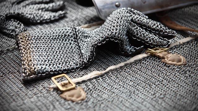 Ein Kettenhandschuh liegt auf einem Kettenhemd, im Hintergrund andere Rüstungsteile.