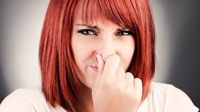 Frau hält die Nase zu