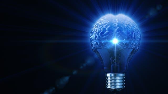 Eine Glühbirne mit blau leuchtendem Gehirn an Stelle von Drähten