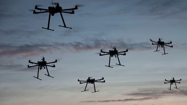 Mehrere Drohnen mit sechs Rotoren im Flug gegen den Himmel fotografiert.