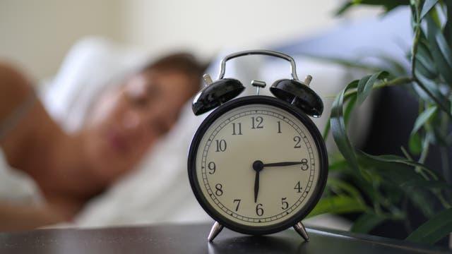 Wecker am Bett zeigt die Uhrzeit: Viertel nach sechs