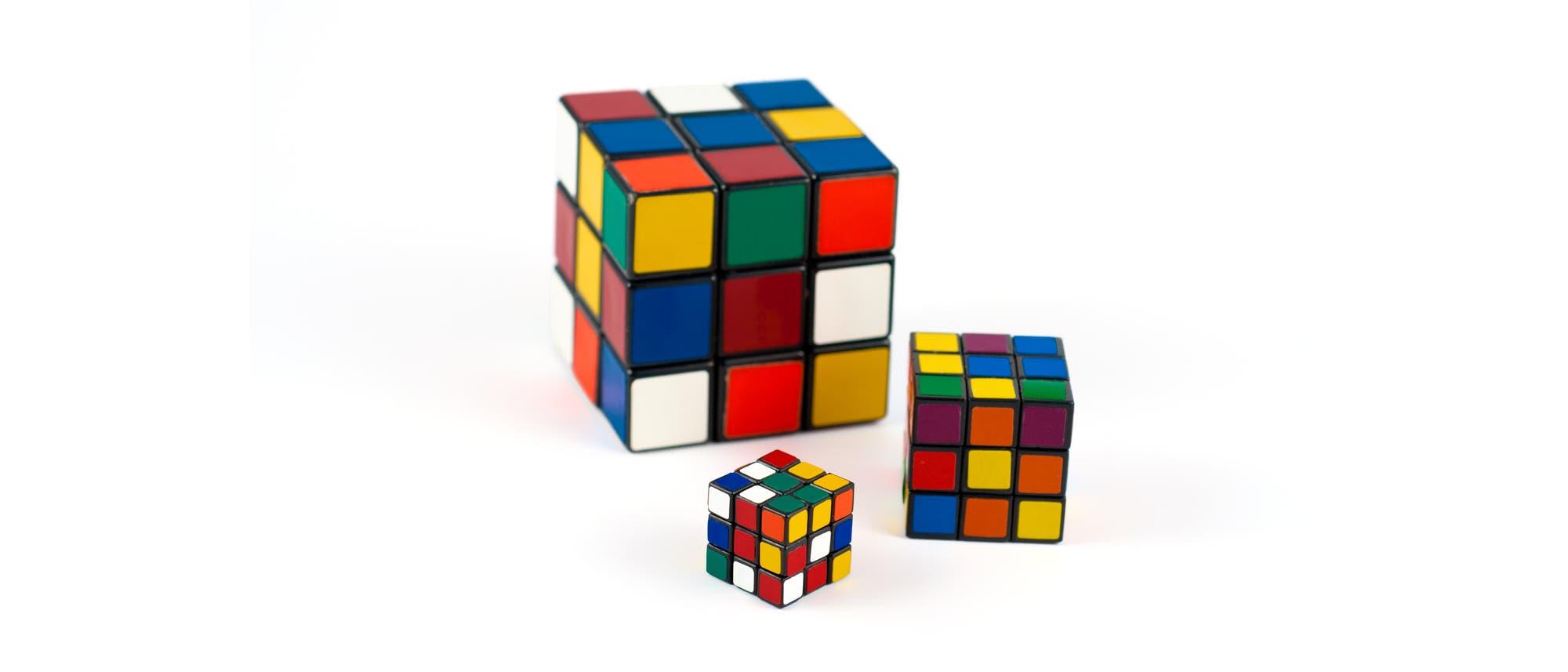 Drei Rubik-Würfel unterschiedlicher Größe auf weißem Grund.