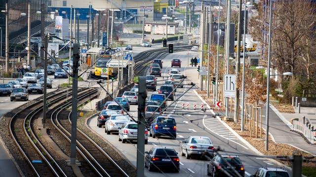 Eine mehrspurige Durchgangsstraße mit Straßenbahnschienen in der Mitte.