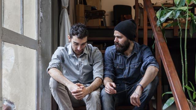 Zwei Männer sitzen auf einer Treppe, der eine schaut bedrückt
