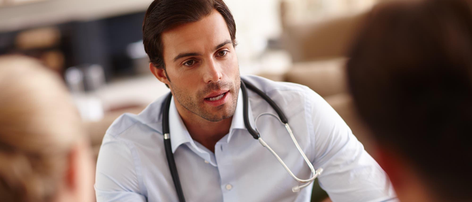 Ein Mediziner im Gespräch mit Patienten