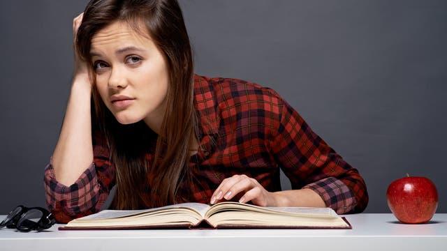 Jugendliche guckt beim Lernen genervt von ihrem Buch auf