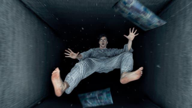 Ein Mann im Pyjama fällt mit Decke und Kissen in einen schwarzen Schacht.
