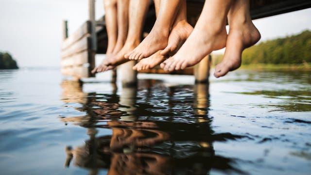 Baumelnde Beine am Badeseesteg