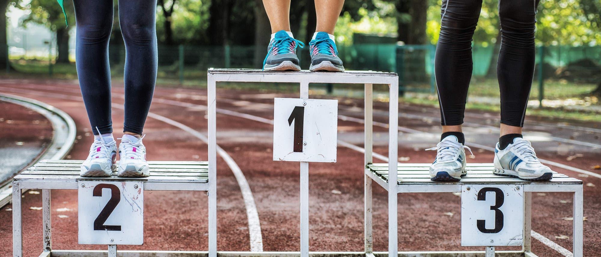 Drei Sportlerinnen stehen auf dem Treppchen
