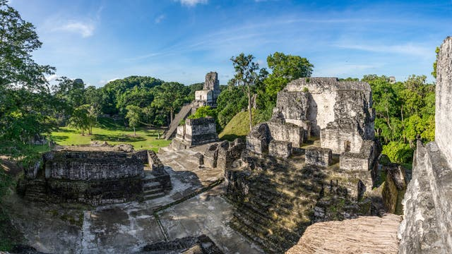Blick von einer bin in mehrere Meter Höhe erhaltenen Maya-Ruine auf die Rasenfläche davor.