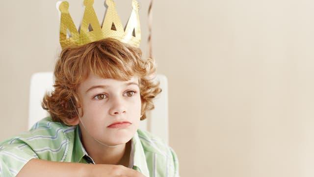 Trauriger Junge mit goldener Papierkrone auf dem Kopf