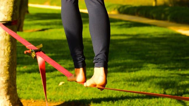 Nackte Füße balancieren auf einem Seil im Park