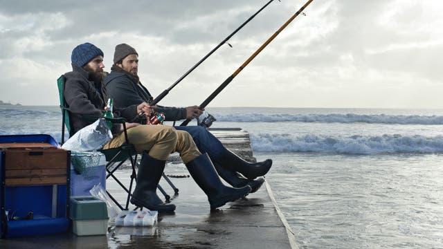 Zwei junge Männer angeln am Meer unter wolkenverhangenem Himmel