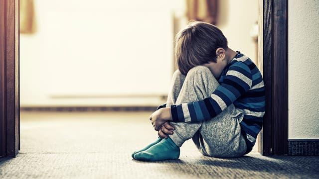 Ein kleiner Junge sitzt zusammengekauert an einer Tür auf dem Boden