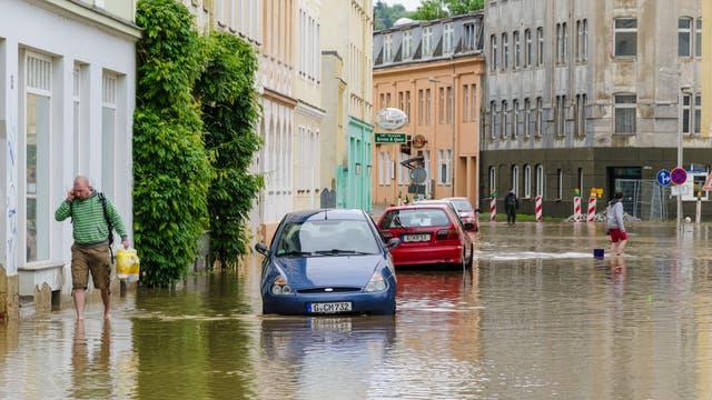 Überschwemmte Straße mit im Wasser stehenden Autos und vermutlich vollgelaufenen Kellern.