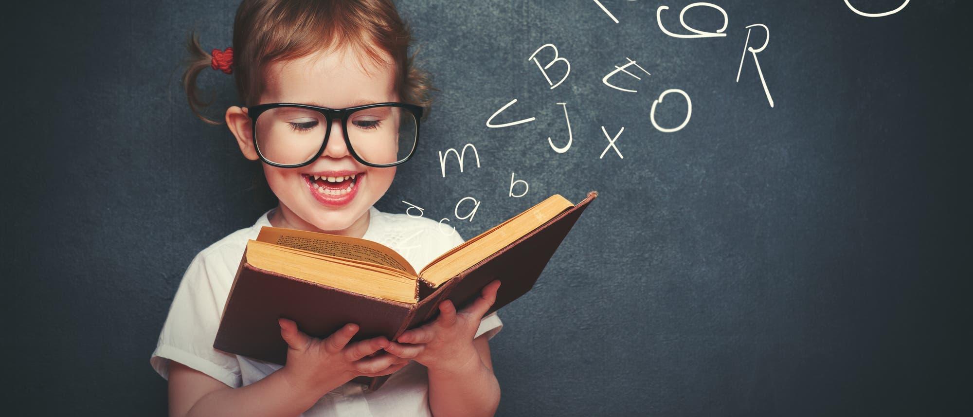 Ein Mädchen liest vor einer Tafel mit Buchstaben in einem Buch