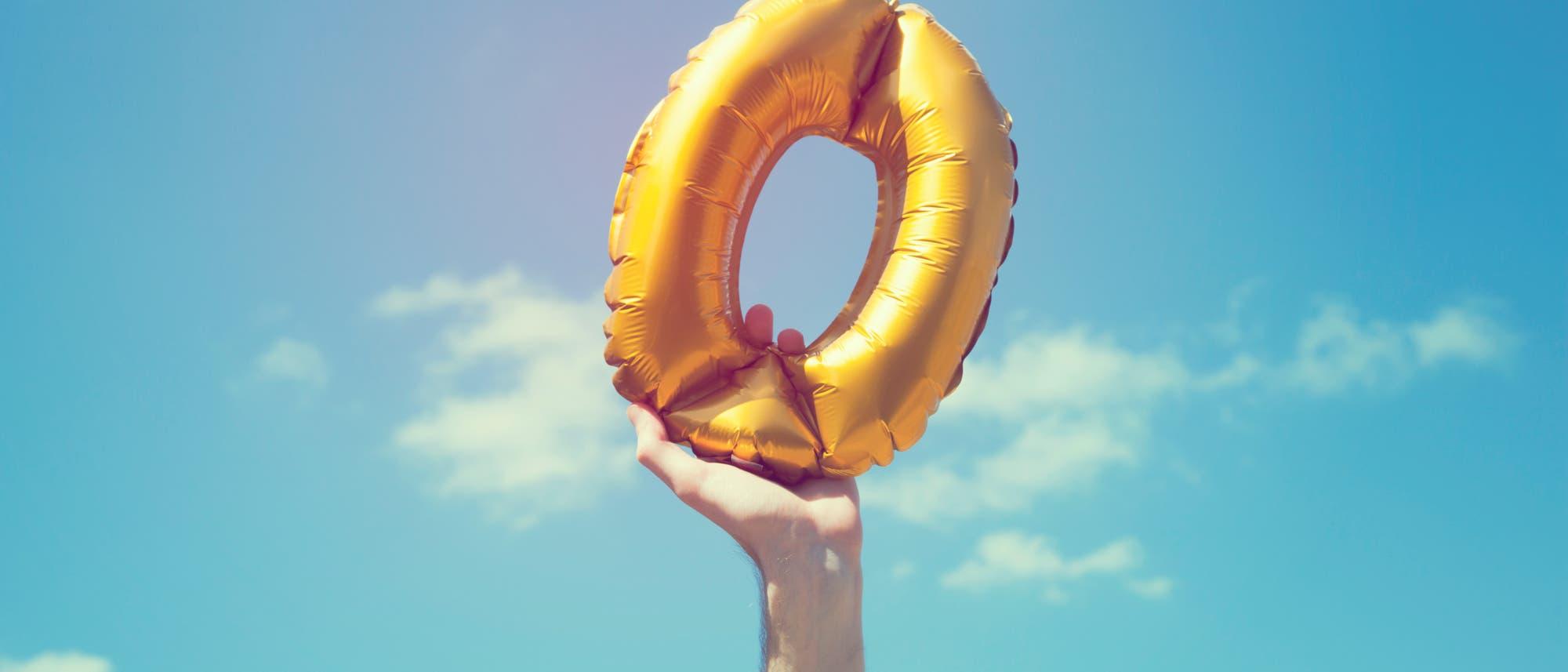 Eine Hand hebt eine goldfarbene aufblasbare Null in den blauen Himmel.