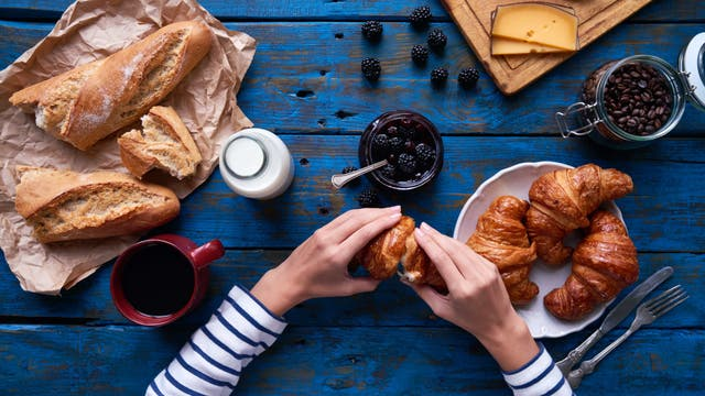 Frühstückstisch von oben: mit Milch und Kaffee, Croissant und Baguette