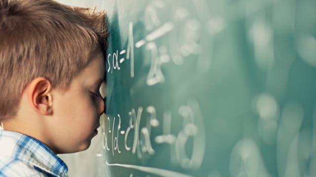Ein Schüler lehnt mit dem Kopf an einer Tafel mit Mathe-Formeln.