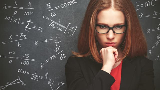Frau mit Brille vor einer Tafel mit Formeln