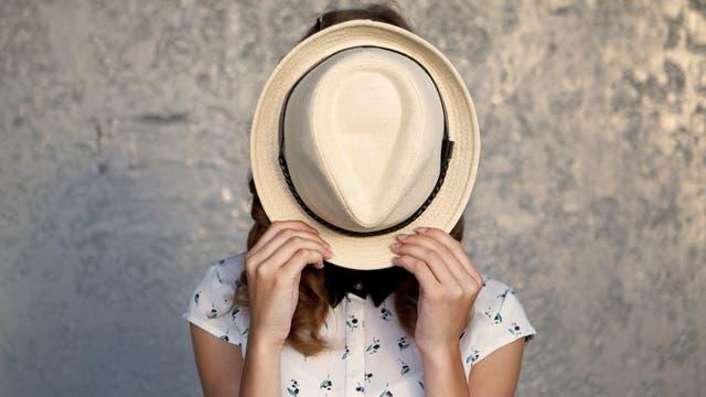 Junge Frau hält sich einen Hut vors Gesicht