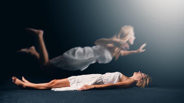 Frau schwebt über ihrem Körper