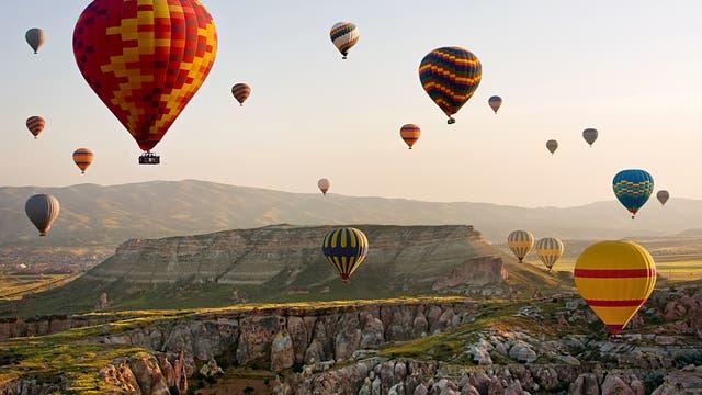 Heißluftballons fliegen über eine Landschaft