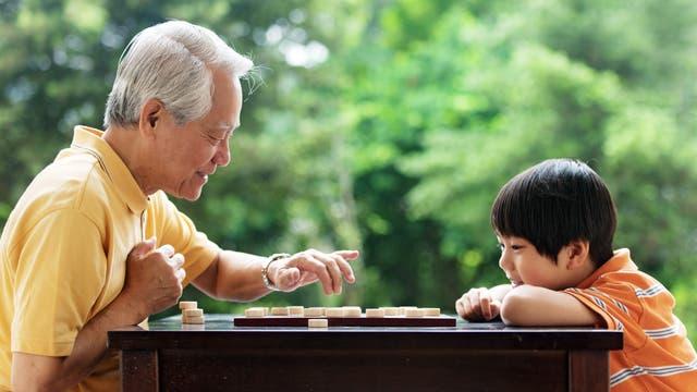 Großvater und Enkelsohn spielen das chinesische Schachspiel Xiangqi