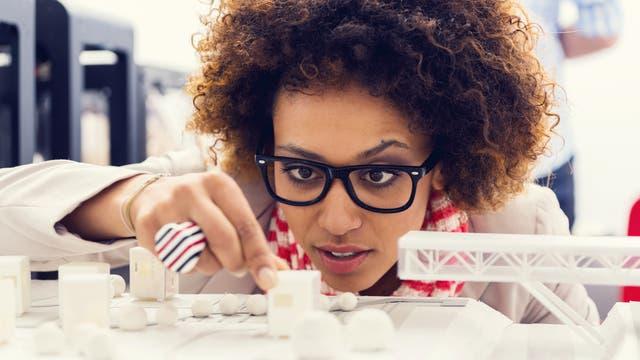 Frau studiert Figuren aus dem 3-D-Drucker