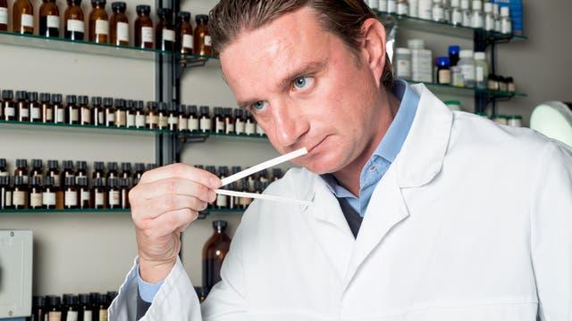 Mann im Kittel riecht an einem Teststreifen