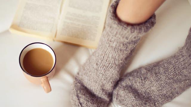 Frauenfüße in grauen Wollsocken, daneben eine Tasse
