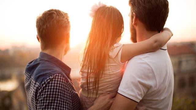 Kind mit zwei Vätern betrachtet einen Sonnenuntergang