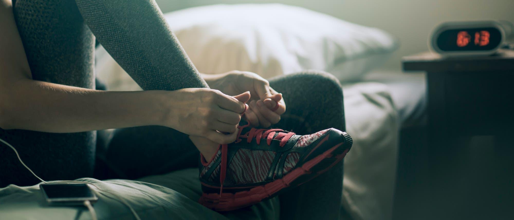 Frau zieht sich morgens am Bett ihre Sportschuhe an