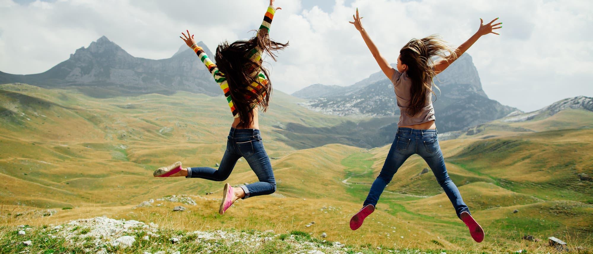 Zwei energiegeladene Mädchen springen vor einer Bergkulisse in die Höhe