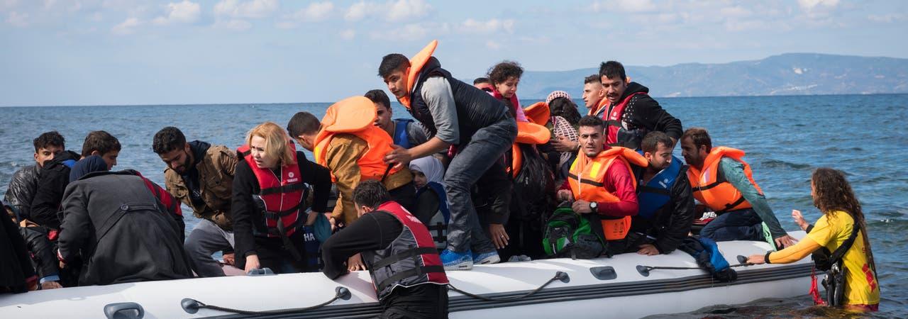 Helfer versuchen ein Schlauchboot zu entladen, in dem sehr viele Menschen sitzen.