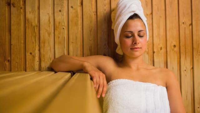 Frau genießt mit geschlossenen Augen ein Saunabad