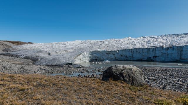 Die Grönländische Eiskappe endet hier in einem Steilabbruch über einem Schuttfächer, durch den sich ein kleiner Schmelzwasserfluss windet.