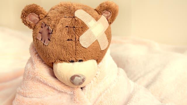 Ein Stoffbär mit Pflastern am Kopf sitzt traurig auf einem Bett