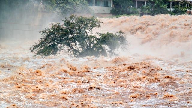 Schlammige Fluten toben durch die Straßen einer tropischen oder subtropischen Stadt.