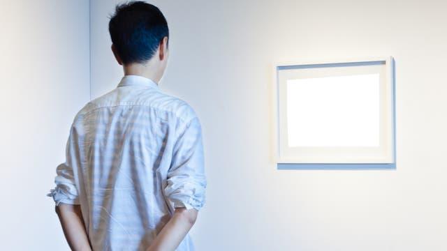 Ein Mann betrachtet Gemälde, auf denen nichts zu sehen ist.