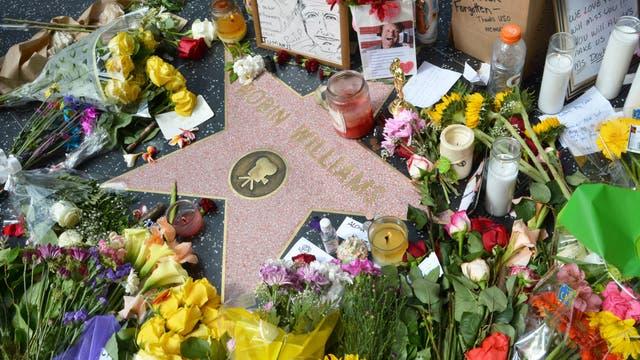 Trauernde legen am Walk of Fame Blumen auf dem Stern von Robin Williams nieder.