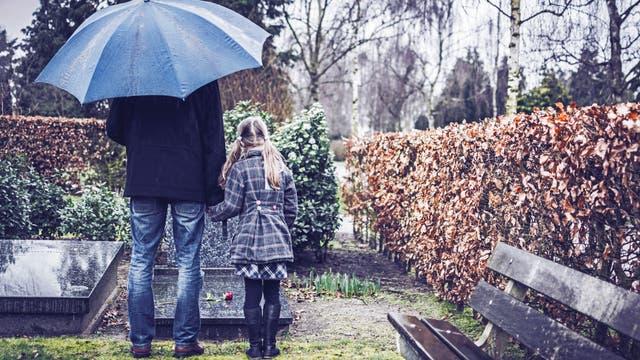 Vater und Tochter stehen an einem Grab