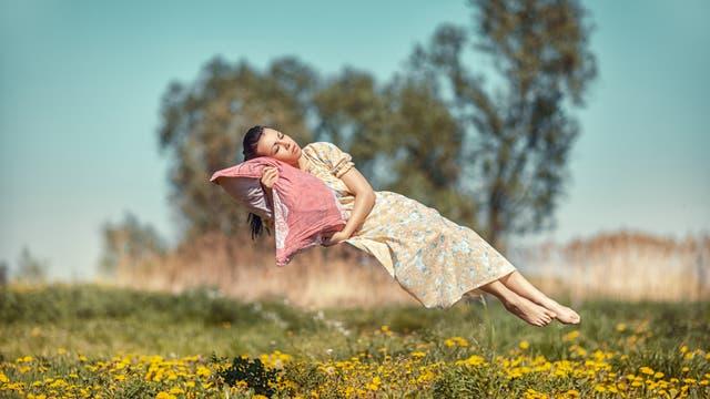 Frau schläft schwebend in der Luft