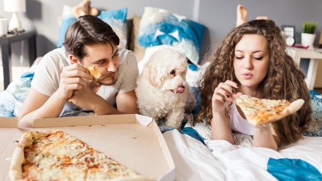 Paar liegt auf dem Bett und isst Pizza. Nein, das ist keine Netflix-Werbung. Nicht mal implizit.