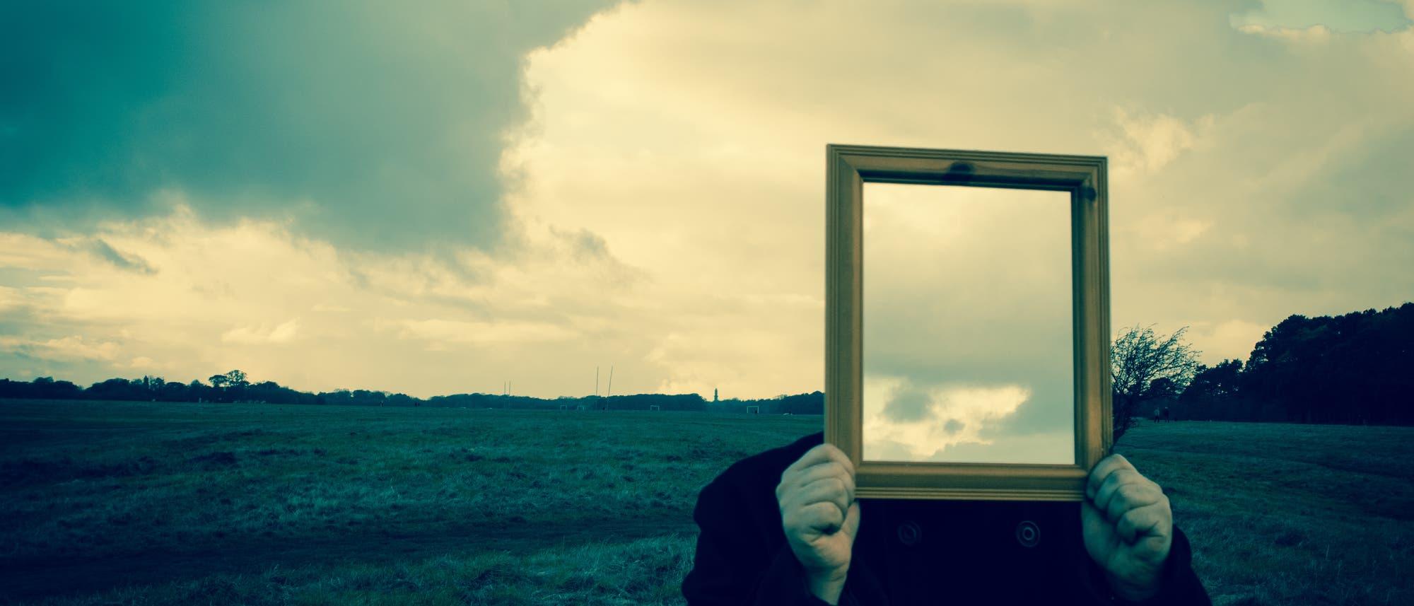 Eine Person hält einen Spiegel vor ihr Gesicht, so dass dieser ihren Kopf ersetzt.
