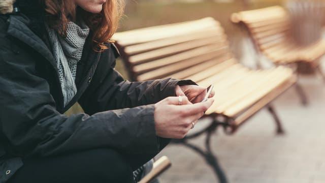 Eine Frau sitzt auf einer Bank und tippt auf dem Handy