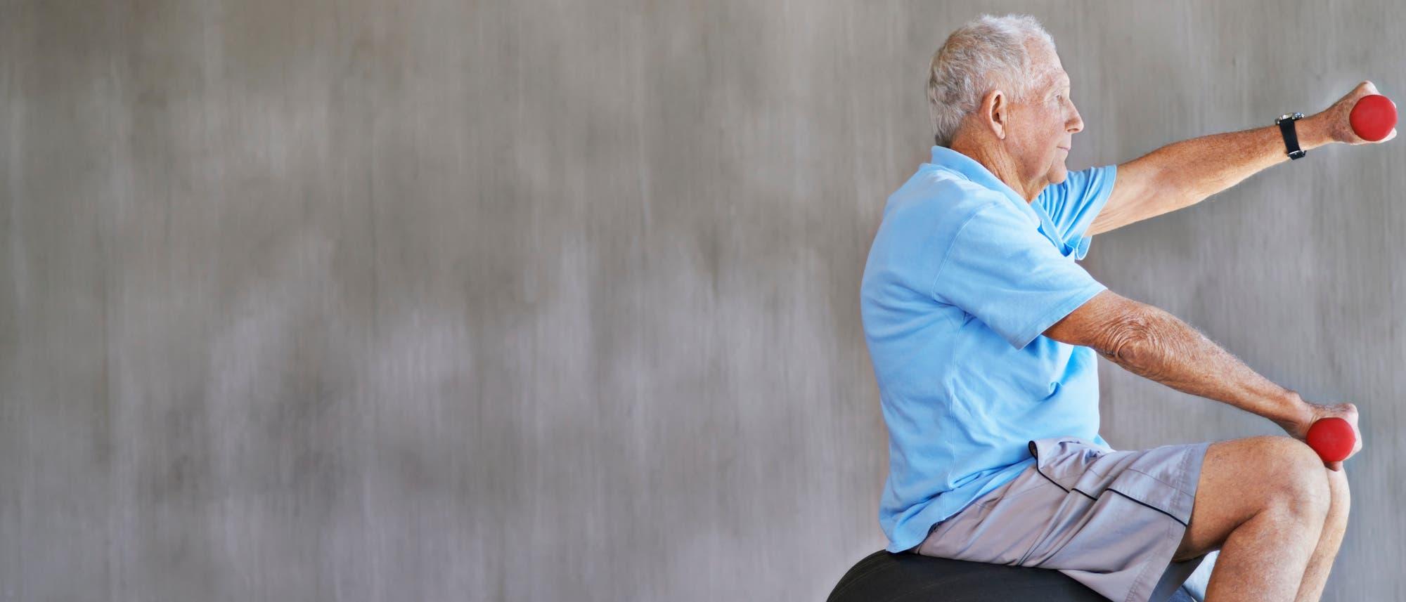 Ein älterer Mann sitzt auf einem Gymnastikball und trainiert mit Kurzhanteln.