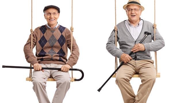 Zwei alte Männer sitzen fröhlich auf Schaukeln