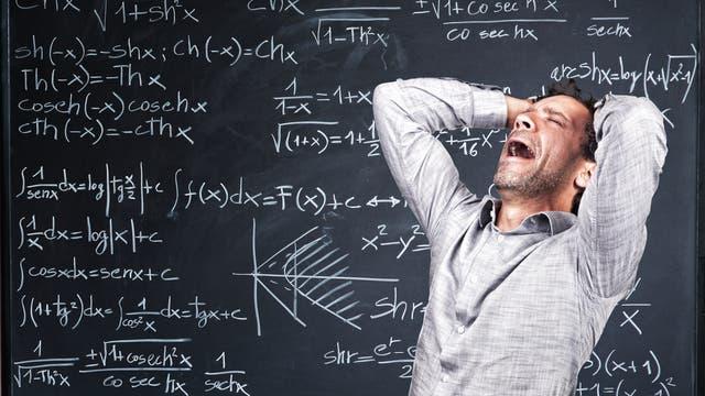 Ein verzweifelter Dreitagebartträger schreit vor dem Hintergrund einer formelbedeckten Schiefertafel seinen Frust über die Unzugänglichkeit der Zahlenwelt heraus