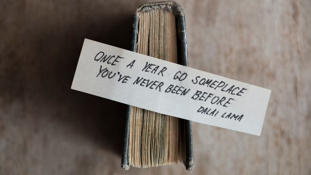 Ein Zettel mit der Aufschrift: »Once a year go someplace you've never been before.» (Dalai Lama)